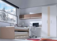 Dormitorio juvenil con armario de 2 puertas largas con franja decorativa (218 x 101) La cama es un mueble compacto con base de 20 cm para colchón de 90 x 190, con nido con ruedas para colchón de 90 x 180 + módulo de 4 cajoncillos.(Incorpora juego de 2 frenos para nido con ruedas)Junto a la cama se ha situado un arcón zapatero de 49 cm de fondo y apertura lateral. La mesa de estudio es una encimera recta de 206 cm de largo, que se apoya sob re el arcón zapatero y sobre un costado para mesa de estudio. Sobre la pared se han colgado 2 módulos de 1 puerta abatible de 103 cm.