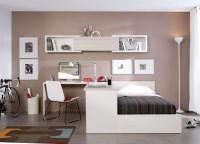 Dormitorio juvenil compuesto por una bañera arcón de apertura lateral para colchón de 90x190; mesa de estudio de rincón con bajos de estantes y cajones vistos a dos caras y una composición de estantes y módulo de puerta a pared.