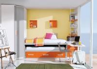 Dormitorio infantil con armario chaflán-recto de 87,5 x 158 y 240 cm de altura (2 puertas). Uno de los costados es más ancho para ubicar el mueble compacto de dos camas con 4 contenedores en la parte inferior del mismo. Sobre la cama se ha realizado una composición mural a base de estanterías cúbicas de 33 x 33 en color a tono con los complementos. La zona de estudio se ha realizado con una encimera recta de 240 de ancho que apoya uno de sus lados sobre un arcón extraíble de dos contenedores y un pie metálico doble en su lado opuesto (se ha incorporado un soporte extensible con ruedas para la CPU). Junto a la mesa de trabajo, se ha colocado también una estantería de 1 m de ancho x 164,5 de altura con soporte de metal y 4 estantes, que descansa igualmente sobre el arcón extraíble. Esta estantería dispone de un panel trasero que en la composición viene terminado en color blanco.