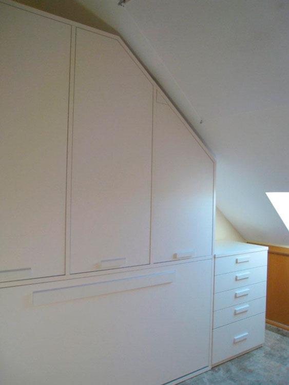 Nos han fabricado especialmente un armario de 270 cm de altura, con cuerpo superior de tres puertas y una cama abatible en la parte inferior. A continuación, se ha colocado un módulo de 4 cajones + un contenedor para prendas más voluminosas
