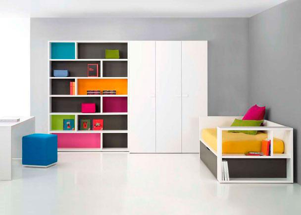 Dormitorio juvenil con librería y armario modular. Original cama nido con lateral abierto que se puede utilizar como mesita de noche o librería.