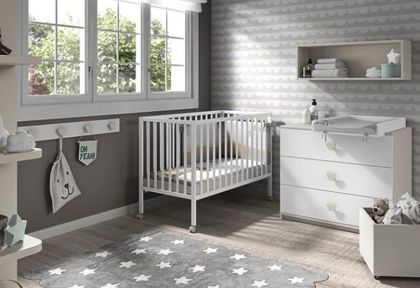 Habitación de bebé con cuna de barrotes de barandilla fija y patas con ruedas. El ambiente se completa con una cómoda de 3 cajones de gran profundi