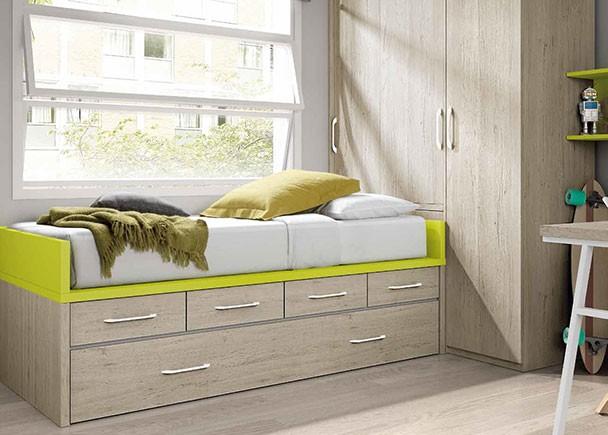 Dormitorio infantil con amplio armario cabina situado en la cabecera de la cama. La cama es un compacto nido con cajones. Junto al armario se situa la