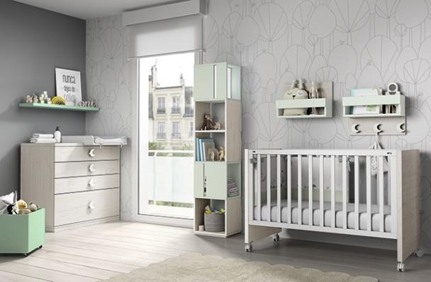 Habitación de bebé con cuna de barrotes de barandilla fija y patas con ruedas. El ambiente se completa con una cómoda con cambiador una estantería